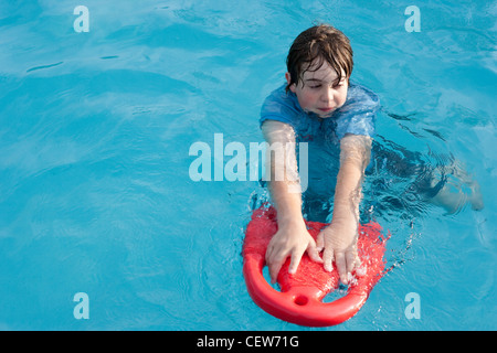 Twelve year old boy floats in swimming pool with a red floatation device. - Stock Photo