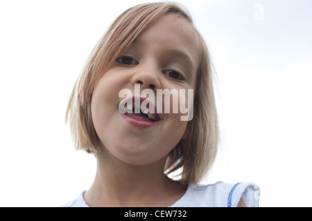 Six year old smiling with large gap, missing front teeth, sky in background. - Stock Photo