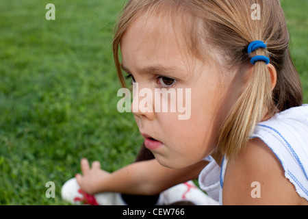 six year old girl sitting in the grass looking serious - Stock Photo