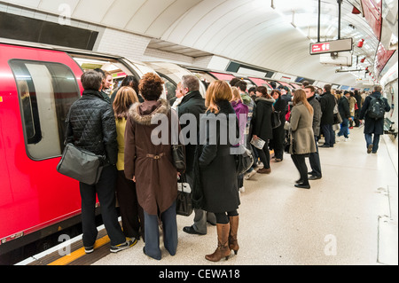Commuters trying to board overcrowded Central Line London Underground carriage during the morning rush hour, UK - Stock Photo
