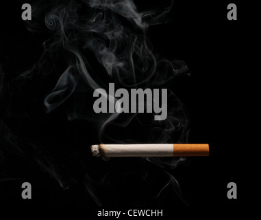 A burning and smoking cigarette on a black background - Stock Photo
