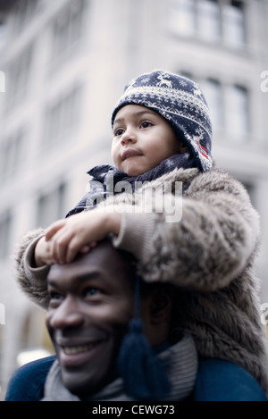 Little girl riding on father's shoulders - Stock Photo