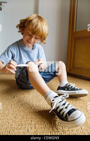 Boy removing adhesive bandage from knee - Stock Photo
