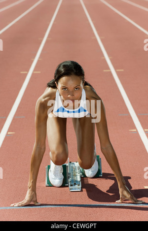 Woman crouched in starting position on running track - Stock Photo