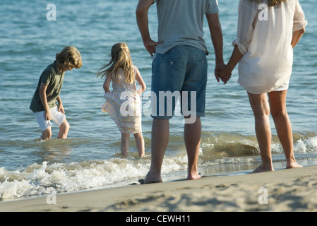 Family at the beach, parents watching as children play in surf - Stock Photo