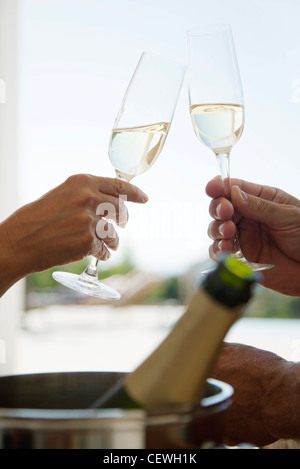 Couple toasting with champagne, cropped - Stock Photo