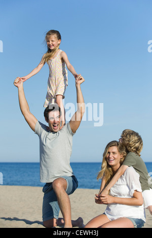 Family playing together at the beach, girl standing on her father's shoulders - Stock Photo