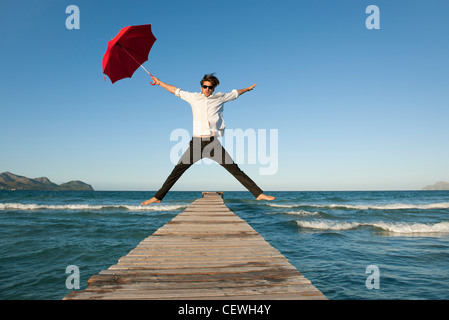 Young man jumping on pier with umbrella - Stock Photo