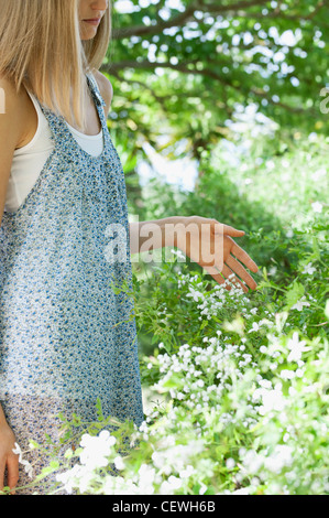 Young woman touching wild flowers, mid section - Stock Photo