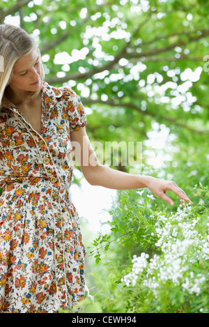 Young woman touching wildflowers - Stock Photo