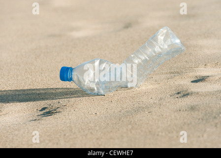 Empty plastic bottle on beach, close-up - Stock Photo