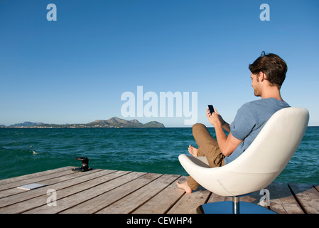Young man sitting in armchair by lake using cell phone, side view - Stock Photo