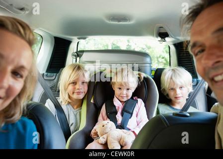 Family in car, smiling at camera - Stock Photo