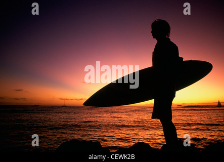 Backlit surfer stands sea with board, Hawaii, USA - Stock Photo