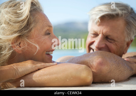 Mature couple relaxing together in pool - Stock Photo