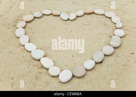 Pebbles arranged in heart shape on sand