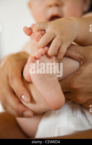 Baby touching its toes, cropped - Stock Photo