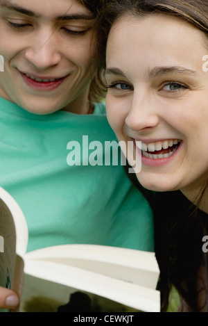 Young couple reading book together, portrait - Stock Photo