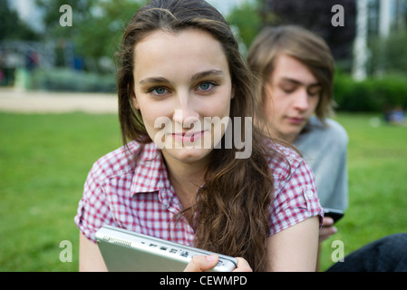 Young woman sitting outdoors, holding laptop computer, portrait - Stock Photo
