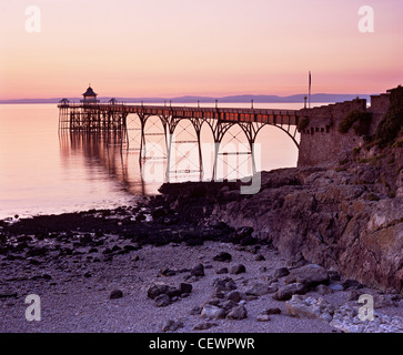 Clevedon pier and the rocky shoreline in warm light. - Stock Photo