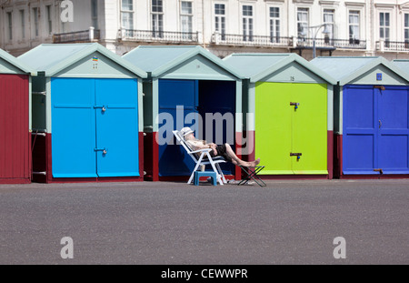 Woman relaxing outside a row of Beach Huts along promenade at Hove near Brighton - Stock Photo