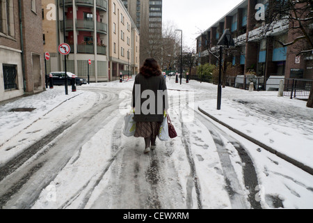 A woman walking along a snowy street in winter wearing shoes with Waitrose shopping bags near Golden Lane in Central - Stock Photo