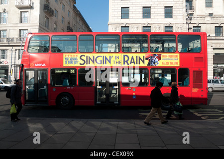 An advertisement for 'Singin' in the Rain' on the side of a 38 double-decker bus on Oxford Street, West End, London - Stock Photo