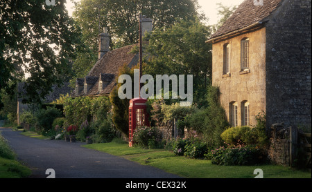 Old fashioned red phone box and village houses in the Cotswold village of Taynton. - Stock Photo
