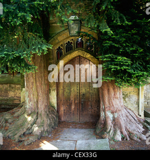 The north door of St. Edwards church with two ancient yew trees either side. - Stock Photo