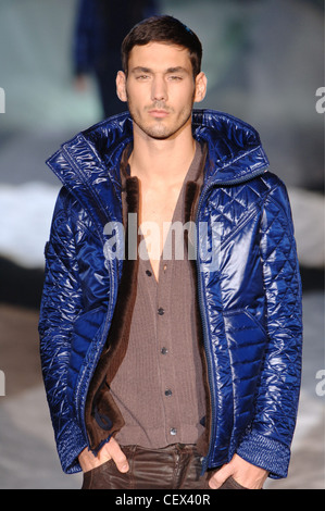 Iceberg Menswear Milan A W Brunette male wearing a shiny puffy short bright blue jacket over a brown cardigan, worn - Stock Photo