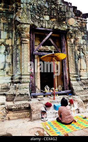 Woman praying in front of a shrine at the Phnom Bakheng temple in Siem Reap, Cambodia - Stock Photo