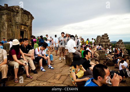 Tourists gathered on top of Phnom Bakheng temple to watch the sunset in Siem Reap, Cambodia - Stock Photo