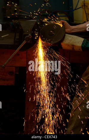 Working blacksmith refining a piece of metal by grinding to smooth the surface.  Sparks are flying from the friction. - Stock Photo