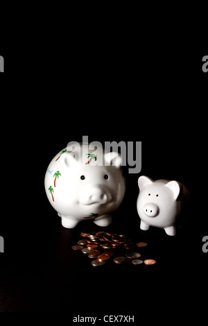 Honeymoon savings Piggy Bank with a small piggy bank and cash on a black background - Stock Photo