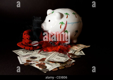 Honeymoon savings Piggy Bank with cash on a black background - Stock Photo