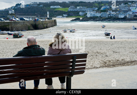A couple sitting on a bench overlooking St Ives Harbour in Cornwall. - Stock Photo