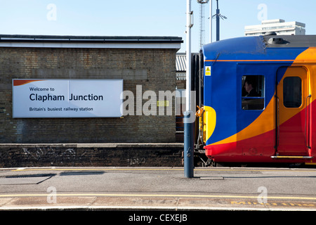 Welcome to Clapham Junction, Britain's busiest railway station. Sign and train at platform, driver in the cab. - Stock Photo
