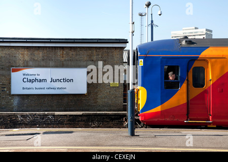 Welcome to Clapham Junction, Britain's busiest railway station. Sign and train at platform with driver leaning out - Stock Photo