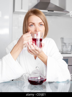 beautiful young woman drinking tea in the kitchen at home - Stock Photo