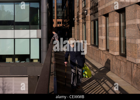 Elderly man walks along modern walkway, past a youthful office worker enjoying a thoughful moment in City of London. - Stock Photo
