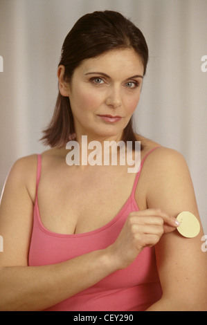 Female brunette hair wearing subtle make up and pink vest top sticking nicotine patch on upper arm looking to camera - Stock Photo