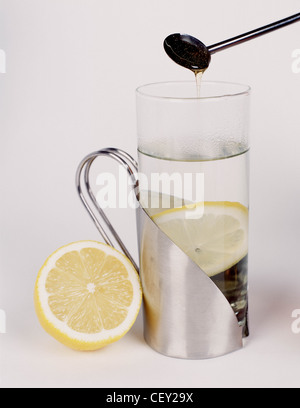 Silver mug with steamed glass containing hot water and a lemon slice silver spoon containing honey held over glass - Stock Photo