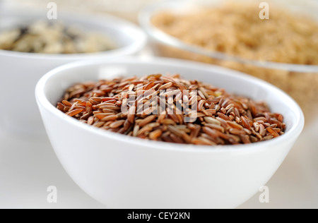Four bowls of different varieties of rice, with a bowl of red rice in the foreground - Stock Photo