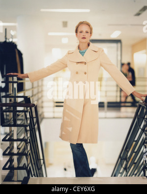 Female blonde hair off face wearing drop earrings, blue top bow at neck under cream double breasted coat and jeans - Stock Photo
