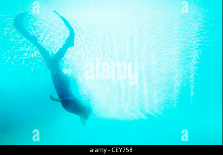 Scuba diver plunging in deep blue water - Stock Photo