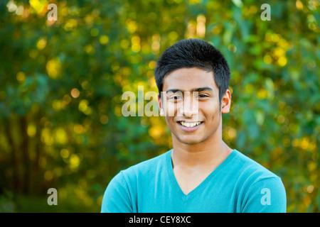 portrait of a teenage boy in a park setting; edmonton alberta canada - Stock Photo