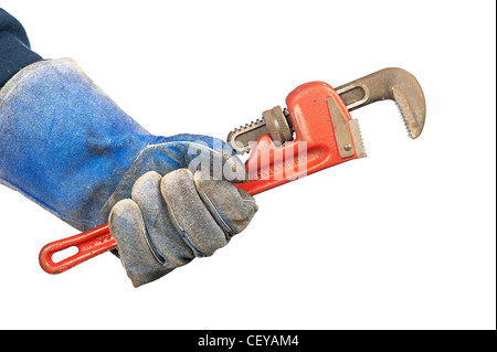 A man holding an old, rusty plumber's pipe wrench while wearing worn out workshop gloves. - Stock Photo