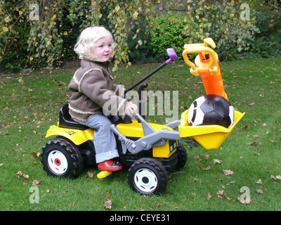 Male child blonde hair wearing a long sleeved brown jacket, jeans and red rubber boots, sitting on a toy JCB digger - Stock Photo