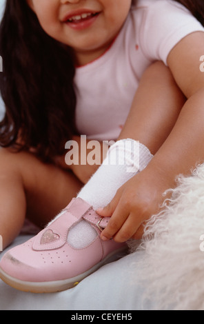 Female toddler with brunette hair, wearing a pink t shirt, face cropped, buckling shoe Ian Boddy - Stock Photo
