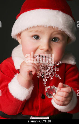 baby in a santa claus outfit chewing on an ornament; edmonton alberta canada - Stock Photo